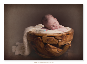 newborn baby girl in puzzle bowl brown seamless background with texture