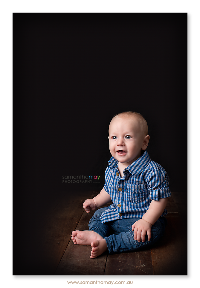 sitting baby boy on black background