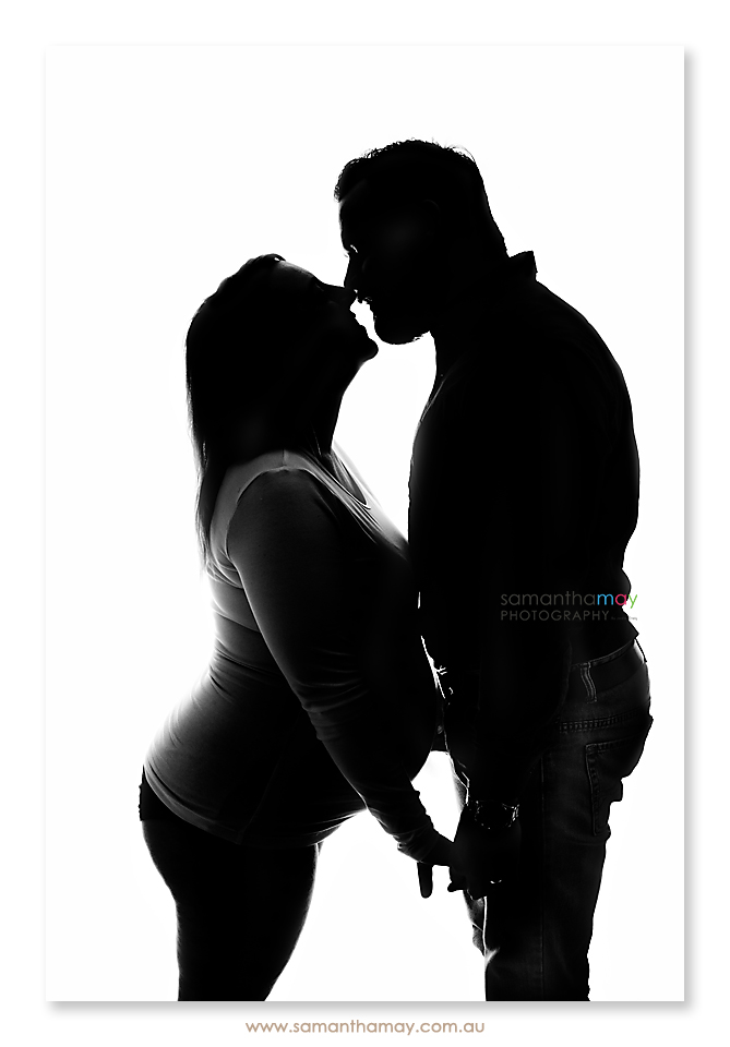 silhouette of pregnant couple kissing