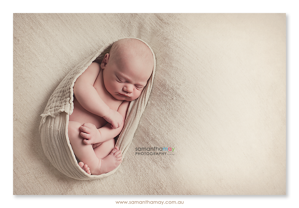 newborn wrapped on his back sleeping