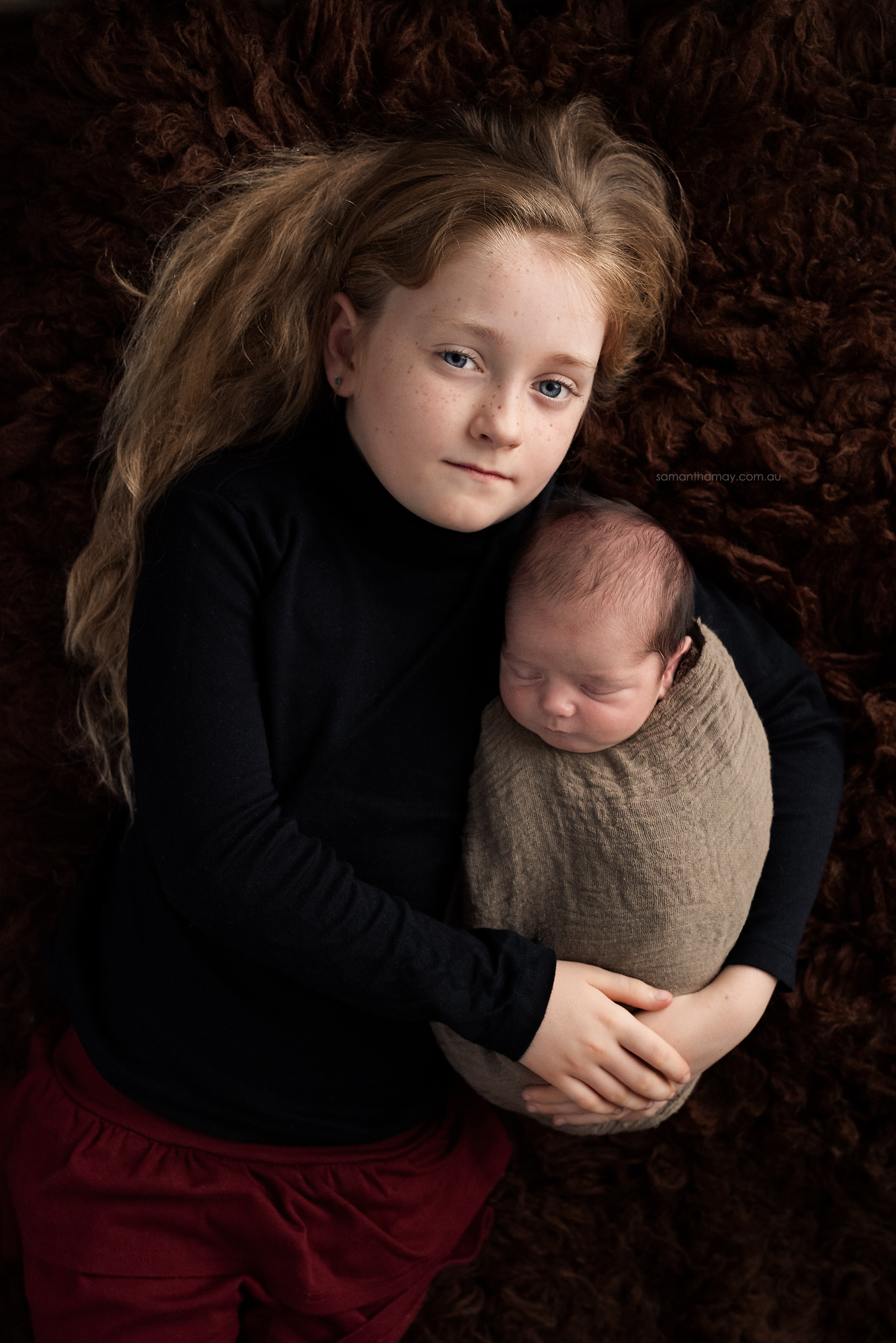 sibling portrait, baby wrapped in big sisters arms on chocolate flokati