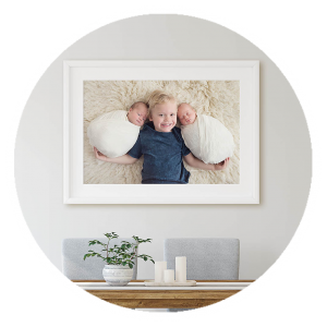 white framed wall art with toddler boy and twin newborn sisters